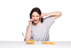 Picture of woman with fruits and hamburger in front on white bac. Natural expressive woman playing with  fries, having in front junk and healthy food, isolated Royalty Free Stock Photos
