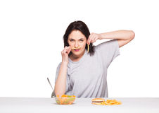 Picture of woman with fruits and hamburger in front on white bac. Natural expressive woman playing with  fries, having in front junk and healthy food, isolated Stock Photos