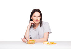 Picture of woman with fruits and hamburger in front on white bac. Natural expressive woman playing with  fries, having in front junk and healthy food, isolated Stock Photo
