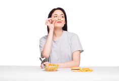 Picture of woman with fruits and hamburger in front on white bac. Natural expressive woman playing with  fries, having in front junk and healthy food, isolated Royalty Free Stock Photography