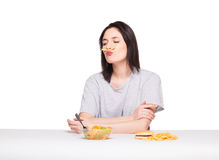 Picture of woman with fruits and hamburger in front on white bac. Natural expressive woman playing with  fries, having in front junk and healthy food, isolated Royalty Free Stock Images