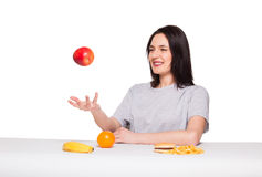 Picture of woman with fruits and hamburger in front on white bac. Natural expressive woman playing with  fruits, having in front junk and healthy food, isolated Stock Images