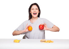 Picture of woman with fruits and hamburger in front on white bac. Natural expressive woman playing with  fruits, having in front junk and healthy food, isolated Royalty Free Stock Photos