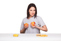 Picture of woman with fruits and hamburger in front on white bac. Natural expressive woman playing with  fruits, having in front junk and healthy food, isolated Royalty Free Stock Images