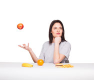 Picture of woman with fruits and hamburger in front on white bac Royalty Free Stock Image