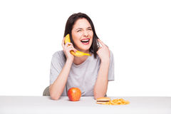 Picture of woman with fruits and hamburger in front on white bac. Natural expressive woman playing with  fruits, having in front junk and healthy food, isolated Royalty Free Stock Image