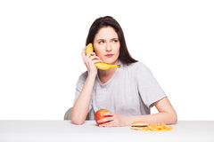 Picture of woman with fruits and hamburger in front on white bac. Natural expressive woman playing with  fruits, having in front junk and healthy food, isolated Stock Photography