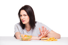 Picture of woman with fruits and hamburger in front on white bac. Picture of woman with fruits rejecting hamburger Stock Image