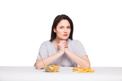 Picture of woman with fruits and hamburger in front on white bac. Picture of woman with fruits and hamburger in front thinking about choice on white background Stock Photos