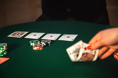 Picture of woman hand that raises cards from the table. In the casino Stock Photography