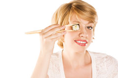 Picture of woman holding sushi rolls on her eyes Royalty Free Stock Images