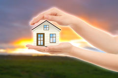 Picture of woman's hands holding a house against nature Stock Images