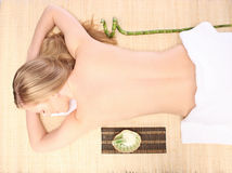 Picture of woman in spa salon lying on the massage desk Stock Photos
