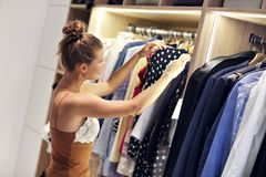 Beautiful woman thinking what to dress in walk-in closet. Picture of woman thinking what to dress in walk-in closet royalty free stock photos