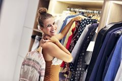 Beautiful woman thinking what to dress in walk-in closet. Picture of woman thinking what to dress in walk-in closet stock images