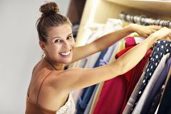 Beautiful woman thinking what to dress in walk-in closet. Picture of woman thinking what to dress in walk-in closet stock photography