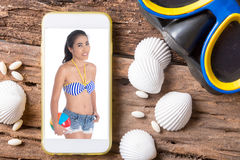 Picture of woman wear swim suit in smart phone and goggles on wo. Picture of woman wear swim suit in smart phone and goggles on old wood floor Stock Images