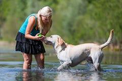 Woman plays with her labrador retriever in a lake Stock Photos