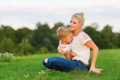 Woman romps with her son on the grass Stock Image