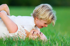 Woman romps with her son on the grass Stock Photography