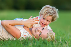 Woman romps with her son on the grass. Picture of a women who romps with her son on the grass Stock Photography