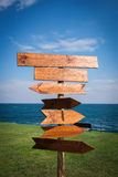 Picture of wooden direction signpost in front of the sea and grass Stock Image