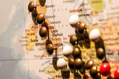 Picture of World Map Travel concept with many pushpins colored pins focus on england. Picture of World Map Travel concept with many pushpins pins focus on stock image