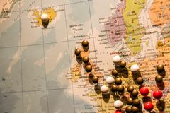 Picture of World Map Travel concept with many pushpins colored pins focus on england. Picture of World Map Travel concept with many pushpins pins focus on stock photography