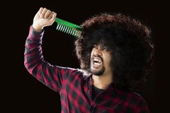 African man combs his frizzy hair. Picture of a young African man looks unhappy while trying to comb his frizzy hair Royalty Free Stock Photography