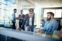 Picture of young architects discussing in office. Picture of young architects discussing in modern office royalty free stock images