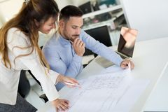 Picture of young architects discussing in office. Picture of young architects discussing in modern office royalty free stock photography