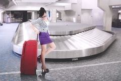 Asian businesswoman with big suitcase at airport. Picture of young Asian businesswoman standing with a big suitcase in the airport terminal Royalty Free Stock Image