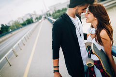 Picture of young attractive couple carrying skateboards Royalty Free Stock Image