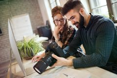 Picture of young attractive designers looking at camera. In office royalty free stock image