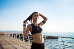 Picture of young attractive fitness girl running with sea coast on background Royalty Free Stock Photo