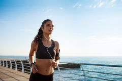 Picture of young attractive fitness girl running with sea coast on background Stock Photos