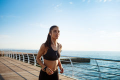 Picture of young attractive fitness girl running with sea coast on background Stock Photography