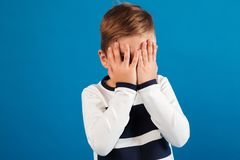 Picture of Young boy in sweater covering his face. Over blue background Royalty Free Stock Photography