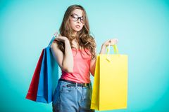Picture of a young brunette woman wearing a pink top and blue jeans posing with shopping bags and looking at camera over blue back royalty free stock photos