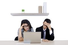 Young business couple having a headache. Picture of a young business couple having a headache while working with a laptop Stock Image
