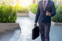 Picture of a young business man walking forward with a briefcase Stock Photos