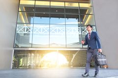 Picture of a young business man walking forward with a briefcase Stock Images