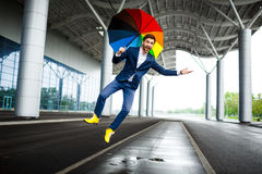 Picture of young businessman holding motley umbrella jumping and having fun at station. Picture of young businessman holding motley umbrella jumping at station stock image