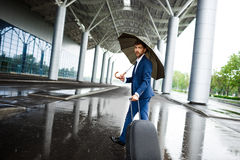 Picture of  young  businessman holding  suitcase and umbrella walking at rainy station Royalty Free Stock Photo