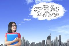 Young businesswoman imagining her wishes. Picture of young businesswoman carrying folders while imagining her wishes and looking at cloud speech bubble in the Royalty Free Stock Photography