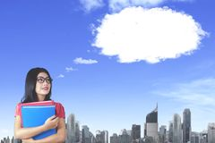 Young businesswoman imagining her wishes. Picture of young businesswoman carrying folders while imagining her wishes and looking at cloud speech bubble in the Royalty Free Stock Photos