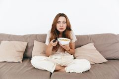 Concentrated amazing pretty lady watch TV. Picture of young concentrated amazing pretty lady sitting on sofa indoors. Looking camera eating corn flakes holding Royalty Free Stock Photo