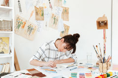 Picture of young concentrated woman fashion illustrator. Image of pretty young concentrated woman fashion illustrator sitting at the table and drawing. Looking stock image