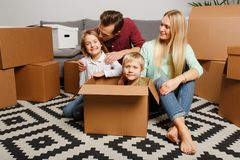 Picture of young couple with children sitting on floor among cardboard boxes stock photography
