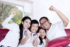 Young family raising hand together at home Stock Image